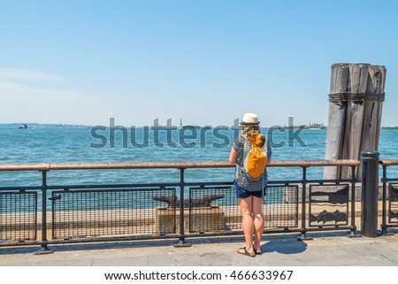 Young tourist looks at Statue of Liberty from Battery Park