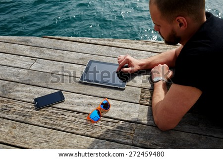 Young tourist man using digital tablet while lying on wooden jetty at marina port during his vacation holidays, man relaxing and enjoying outdoors while reading digital e-book on touch pad - stock photo