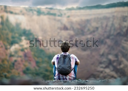 Young tourist man with backpack sitting on rocky cliff and enjoying beautiful view - stock photo