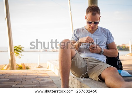 Young tourist sitting under palm tree with mobile phone and listening to music. Positive emotion. Vacation time. - stock photo