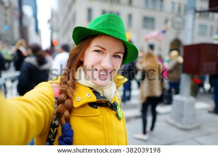 Young tourist taking a selfie with her smartphone during the annual St. Patrick's Day Parade on 5th Avenue in New York City - stock photo