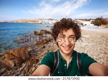Young tourist taking selfie on Mykonos beach with Little Venice in the background. Mykonos, Greece.  - stock photo