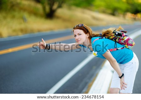 Young tourist with a backpack hitchhiking along a road - stock photo