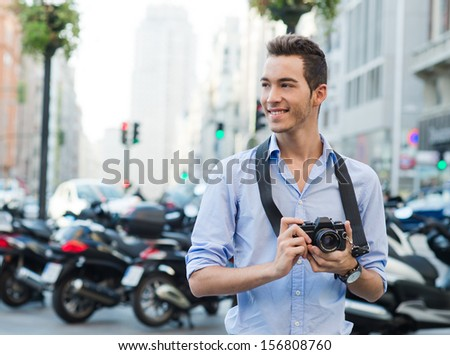 YOung tourist with a camera looking to take a pic - stock photo