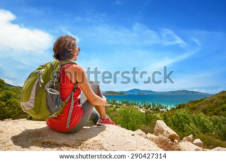 Young tourist with backpack relaxing on top of the mountain and enjoying beatiful coast view.