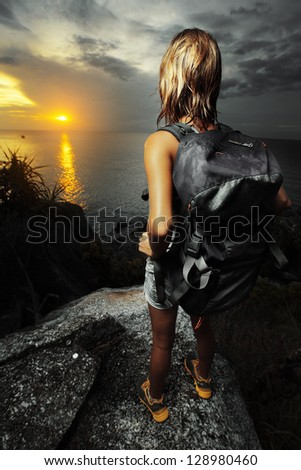 Young tourist with backpack standing on a rock and watching sunset over sea - stock photo