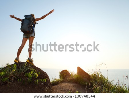 Young tourist with backpack standing on a rock with raised hands - stock photo