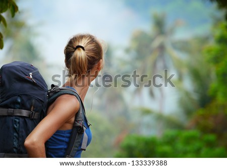 Young tourist with backpack walking in tropical forest - stock photo