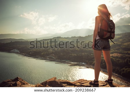 Young tourist woman on the top of the mounting with pleasure looking at a beautiful sea landscape and sun