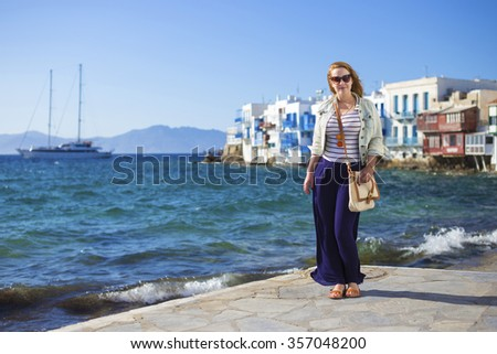 Young tourist  woman standing at the beach of Mykonos with Little Venice and sailboat at the background - Greece - stock photo