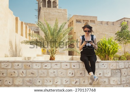Young Tourist Woman Taking Rest During Sightseeing And Using Smart Phone - stock photo
