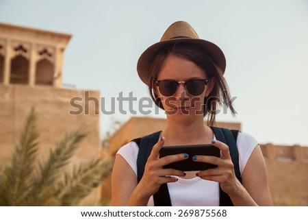 Young Tourist Woman Using Smart Phone And Enjoying Sightseeing Landmark - stock photo