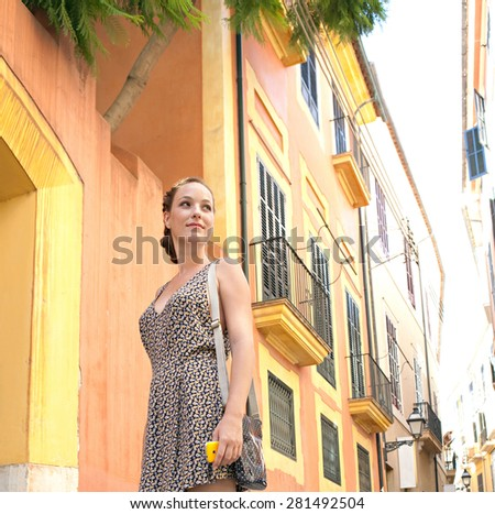 Young tourist woman visiting a picturesque destination city street, contemplating the architecture and carrying a smart phone on a summer holiday, outdoors. Travel lifestyle and technology weekend. - stock photo