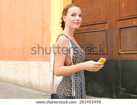 Young tourist woman visiting a picturesque destination city street, using a smart phone walking a tourist street with a large wooden door on a summer holiday, outdoors. Travel technology lifestyle.