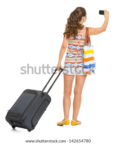 Young tourist woman with wheel bag taking photo . rear view - stock photo