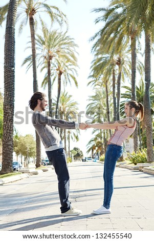Young touristic couple being playful in a palm trees boulevard, holding hands and leaning back, trusting each other while on holiday.