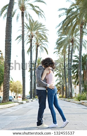 Young touristic couple hugging in a palm trees boulevard while visiting a destination city on holiday.