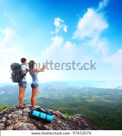 Young tourists with backpacks taking photo of a valley from top of a mountain - stock photo