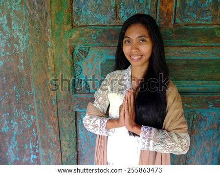 Young traditional Asian woman greeting in front of wooden house.