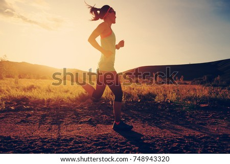 young trail runner woman running on sunset forest