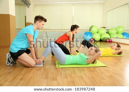 Young trainer and woman engaged in gym