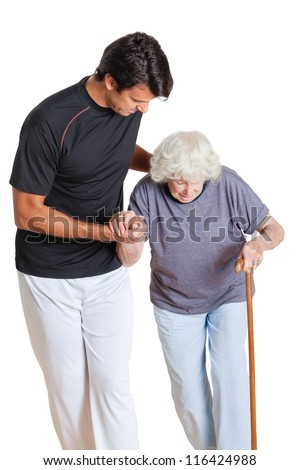Young trainer assisting senior woman holding walking stick over white background - stock photo