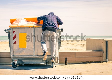 Young tramp rummaging in trash container looking for food and reusable goods - Modern concept of poverty with normal citizens becoming suddenly poor - Economy crisis and people with living issues - stock photo