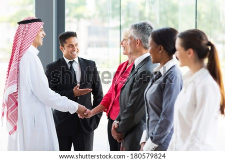 young translator introducing Arabian businessman to business partners - stock photo