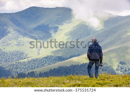 Young traveler admiring stunning view in mountains, holding camera in his hand - stock photo