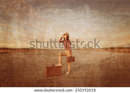 Young traveler hipster woman with retro suitcase looks through binoculars on road. Vintage image - stock photo