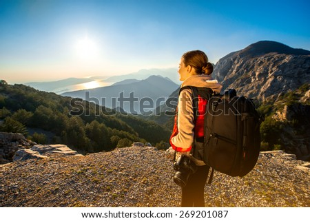 Young traveler photographer with photo camera and backpack standing on the top of mountain and looking on the sunset