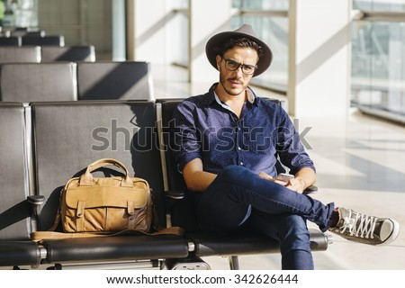 Young traveler sitting in an airport, with a leather briefcase and his smartphone - stock photo