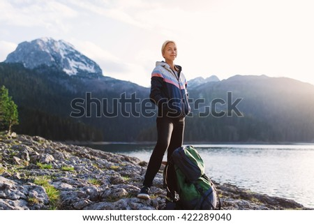 Young traveler standing with her backpack near mountain lake while hiking  - stock photo