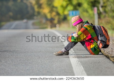 Young traveler tired sitting on the road waiting for car. daylight - stock photo