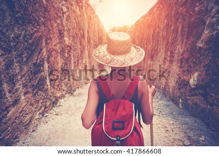 Young traveler walking through rock canyon. Intentional sun glare and vintage color - stock photo