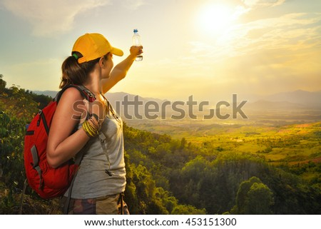 Young traveler with a backpack standing on a mountain top enjoying sunset. - stock photo