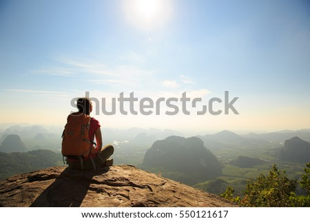 young traveler with backpack sit on the mountain peak rock observing locality
