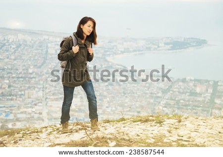 Young traveler woman with backpack walking in highlands over the city. Hiking and recreation theme - stock photo