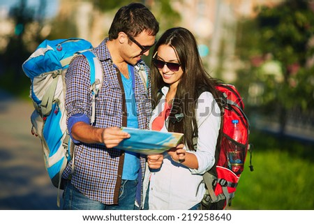 Young travelers studying map outdoors - stock photo