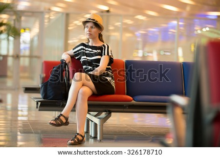 Young traveling woman in summer dress and straw hat waiting for trip, sitting with thoughtful expression in modern station lounge area with blue and red seats, full length - stock photo