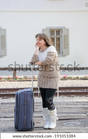 Young traveling woman standing with suitcase along the train tracks, smiling - stock photo