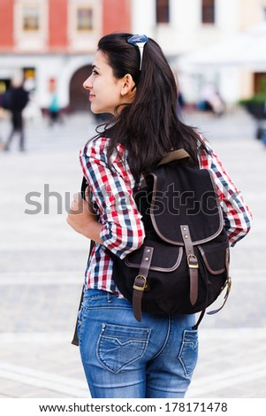 Young traveller with backpack visiting a city. - stock photo