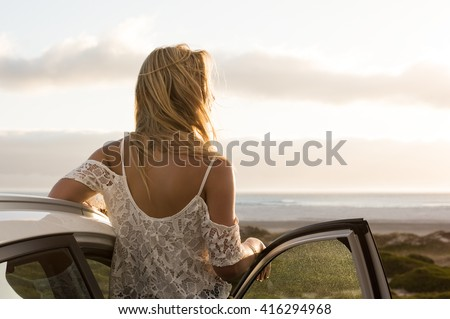Young traveller woman enjoying sunset standing outside car. Serene woman leaning on car during sunset. Young woman on summer travel to the coast. - stock photo