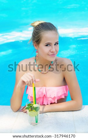Young trendy blonde woman with a glass of refreshing lemonade smiling happily in the swimming pool