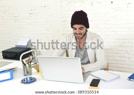 young trendy businessman in cool hipster beanie look smiling confident and working happy at modern home office with computer as creative designer in freelance business success concept - stock photo