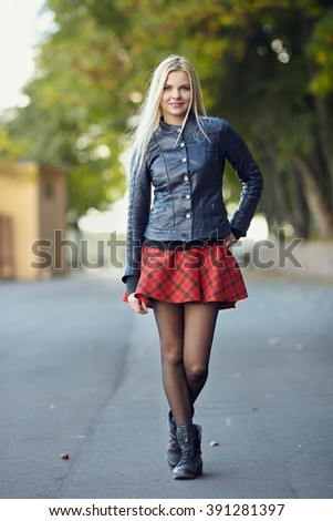 Young trendy dressed blonde woman showing her weekend outfit having fun and posing on park path shallow depth of field