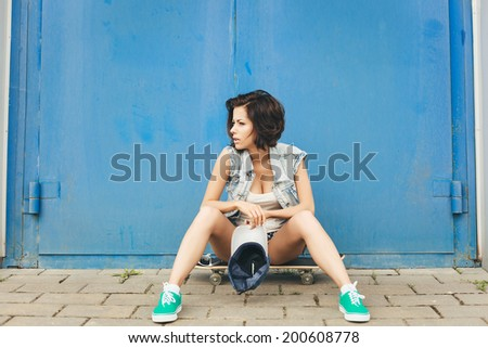 Young trendy girl with skateboard on the background of blue wall. Outdoor lifestyle portrait