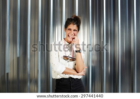 Young trendy hipster woman smiling for the camera in pose with hands crossed while standing on shiny chrome background with copy space for your text message, smiling and cheerful woman looking away - stock photo