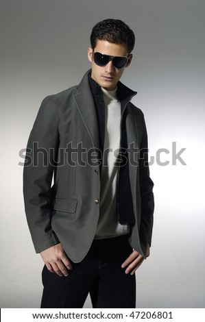young trendy male model wearing sunglasses