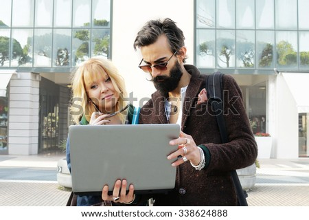young trendy man and woman with laptop computer stand outside office discussing - 2 busy colleagues discussing work project - busy architects, business people or work-oriented IT professionals outside - stock photo